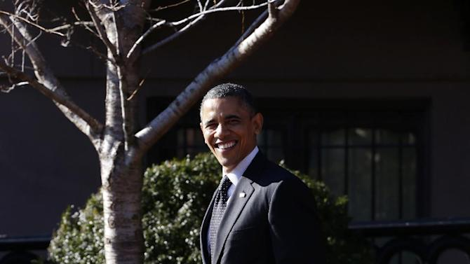 President Barack Obama smiles as he looks towards reporters shouting questions at him regarding the fiscal cliff as he walks from Blair House back to the White House in Washington, Thursday, Dec. 13, 2012, after attending a holiday party for the National Security Council. (AP Photo/Charles Dharapak)