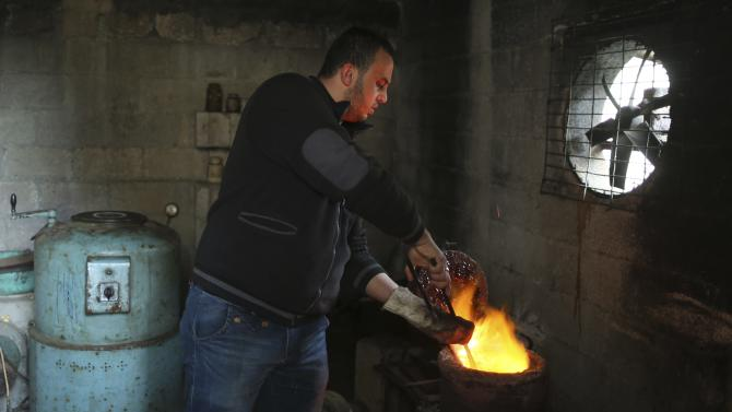 A Palestinian worker melts gold at a jewellery workshop in Gaza City