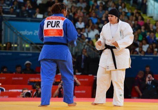 Saudi Arabia&#39;s Wojdan Shaherkani (in white) competes with Puerto Rico&#39;s Melissa Mojica in the +78kg judo class at the London Olympics. The father of the first ever Saudi female to compete at the Olympic Games has vowed to sue those who insulted his daughter for challenging strict traditions that prevented women from participating
