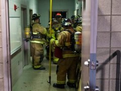 Fire fighters inspect the East High electrical room — Salt Lake Tribune