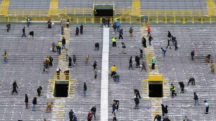 Paid volunteers clear snow from the bleachers at Lambeau Field in Green Bay, Wisconsin