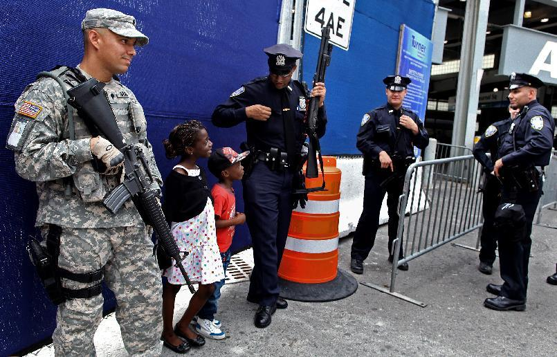 A Port Authority police officer shares a light moment with children visiting from France at commuter train station near ground zero Saturday, Sept. 10, 2011 in New York. Heavily armed police remained a visible presence around New York on the eve of the 10th anniversary of the World Trade Center attacks. (AP Photo/Craig Ruttle)