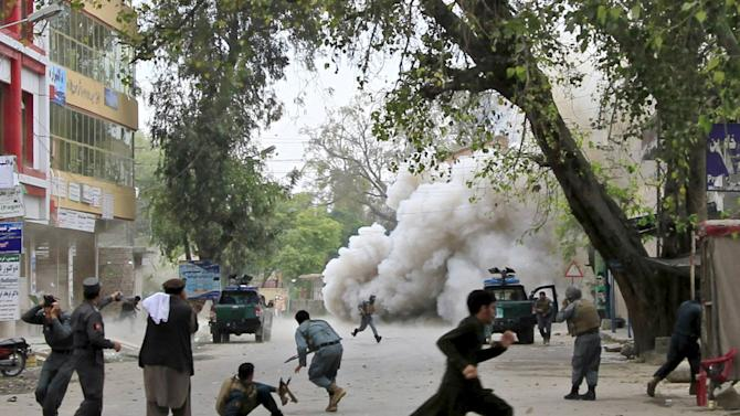 People run for cover after an explosion in Jalalabad