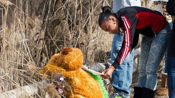 Mindy Morgan reads a note at the memorial where six teens were killed in a car crash on Park Ave. in Warren, Ohio on Sunday, March 10, 2013. (AP Photo/Scott R. Galvin)