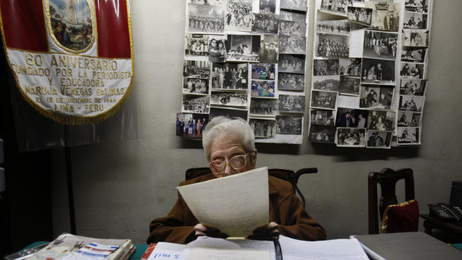 "In this Nov. 26, 2012 photo, journalist and radio host Maria Julia Venegas, better known as Maruja Venegas, 97, reads during an interview at her home in Lima, Peru. Venegas who began broadcasting ""Radio Club Infantil,"" a show for Peru's children in the golden age of radio and World War II, has earned a citation from Guinness World Records as the globe's longest-running radio personality. (AP Photo/Karel Navarro)"