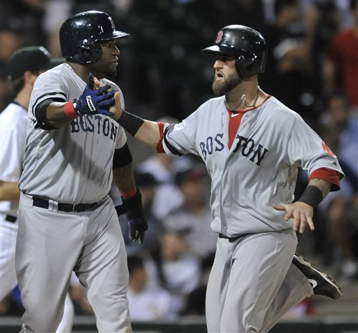 Boston Red Sox's Mike Napoli right, celebrates with teammate David Ortiz left, at home plate after both scored on a Will Middlebrooks' double during the seventh inning of a baseball game against the C