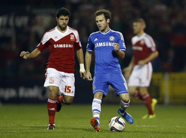 Chelsea's  Juan Mata, right, vies for the ball with Swindon's Yaser Kasim during the English League Cup soccer match between Chelsea and Swindon Town at the County Ground in Swindon, England Tuesday,