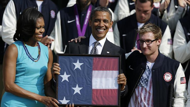 President Barack Obama and first lady Michelle Obama are presented with the U.S. Olympic flag by Navy Veteran Brad Snyder, during a ceremony on the South Lawn of the White House in Washington, Friday, Sept. 14, 2012, welcoming the 2012 U.S. Olympic and Paralympic teams. (AP Photo/Pablo Martinez Monsivais)