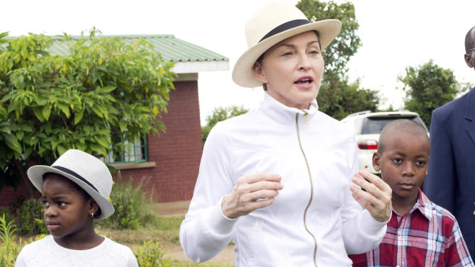 AP10ThingsToSee - Madonna, center, tours the Mphandura orpahange near Lilongwe, Malawi on Friday, April 5, 2013. The performer is spending her fourth day in the southern African country from where she adopted two children David Banda, right and Mercy James, left. (AP Photo/Thoko Chikondi, File)