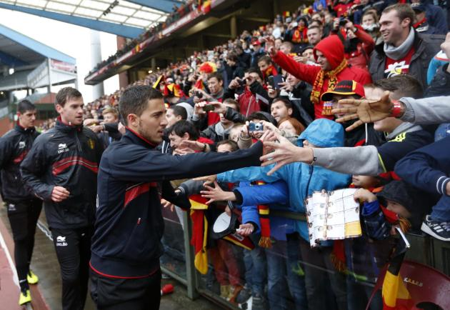 Belgium's soccer team players Hazard, Lombaerts and Courtois greet supporters during a training session in Brussels