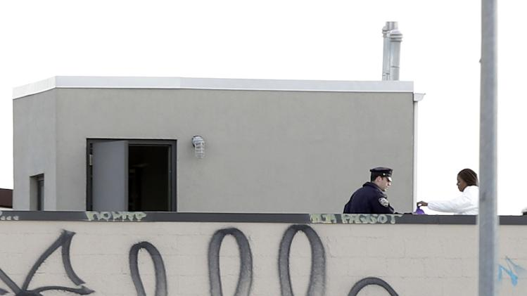 "CORRECTS TO CLARIFY RELATIONSHIP BETWEEN SHOOTER AND VICTIMS - Police officers and crime scene personnel work on the roof of a building in the Brooklyn section of New York, Monday, Nov. 11, 2013. A musician shot and killed two members of an Iranian indie rock band, the Yellow Dogs, and a third musician early Monday, and wounded a fourth person at their apartment before killing himself on the roof, police and the group's manager said. The shooter was a member of another band from Iran, the Free Keys, who knew the victims but hadn't spoken to them in months because of a ""petty conflict,"" according to Yellow Dogs manger Ali Salehezadeh. (AP Photo/Seth Wenig)"