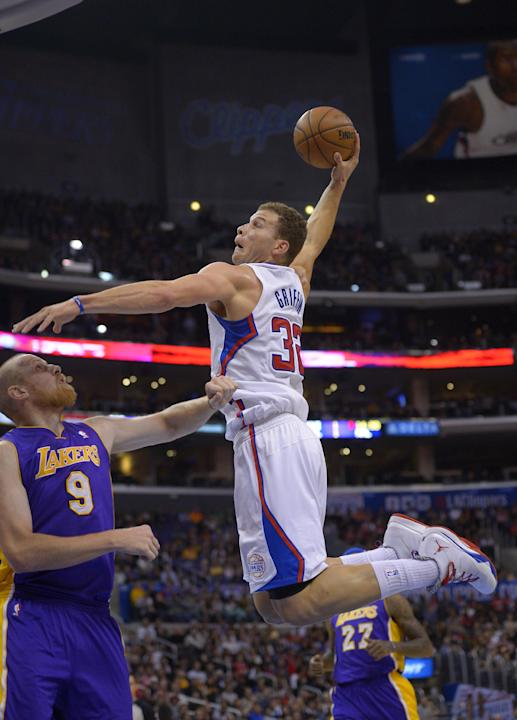 Los Angeles Clippers forward Blake Griffin, right, goes up for a dunk as Los Angeles Lakers center Chris Kaman defends during the first half of an NBA basketball game, Friday, Jan. 10, 2014, in Los An