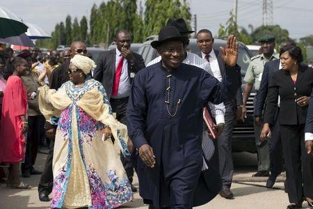 Nigeria's President Goodluck Jonathan and wife waves to people in the queue waiting to cast their vote in Otuoke