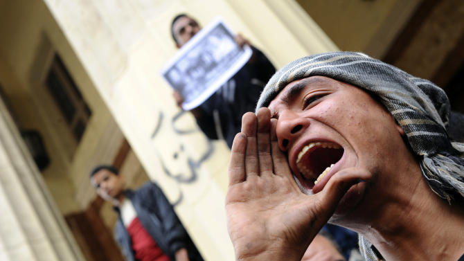 A protester chants slogans near a Cairo court where supporters of the April 6 youth group gathered to condemn the detention of 24 activists arrested Tuesday while taking part in a protest that was not authorized by authorities, in Cairo, Egypt, Saturday, Nov. 30, 2013. A top Egyptian government official, Deputy Prime Minister Ziad Bahaa-Eldin, strongly denounced a new protest law Saturday as police fired tear gas and used batons to beat back stone-throwing demonstrators in Cairo. (AP Photo/Ahmed Omar)