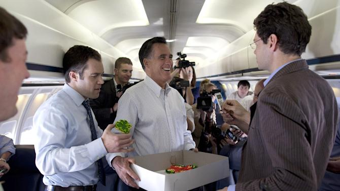 Republican presidential candidate, former Massachusetts Gov. Mitt Romney hands out cookies before departing on a flight to the next campaign stop, Tuesday, March 13, 2012, in St. Louis, Mo.  (AP Photo/Evan Vucci)