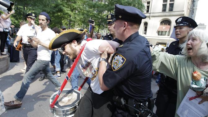An Occupy Wall Street protestor is arrested in Zuccotti Park Wednesday, July 11, 2012, in New York. Occupy marchers with guitars are marking the 100th birthday of the late folk singer-songwriter Woody Guthrie with a Manhattan rally. It's called Occupy Guitarmy They ended a six-day march from the Liberty Bell in Philadelphia on Wednesday afternoon in Zuccotti Park. The lower Manhattan park was the center of the Occupy movement until police broke up the encampment last November.  (AP Photo/Frank Franklin II)
