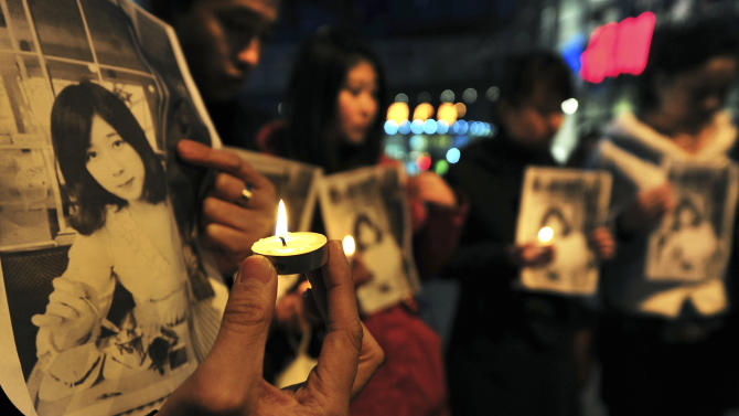 In this Wednesday, April 17, 2013 photo, Chinese hold pictures of Lu Lingzi, a Boston University graduate student from China who was killed Monday in the Boston Marathon explosions, as they hold candles to mourn for her in Shenyang in northeast China's Liaoning province. Lu was a graduate student studying mathematics and statistics and scheduled to receive her graduate degree in 2015. (AP Photo) CHINA OUT