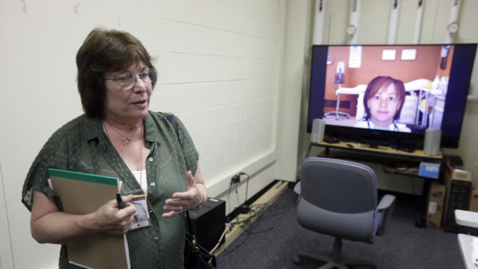In this Thursday, July 18, 2013 photo, Nadine Martin, a communication sciences professor speaks in view of an avatar on a television screen during an interview with the Associated Press at Temple University in Philadelphia. Martin and other researchers are working to develop a virtual speech therapist to help those trying to overcoming the language disorder known as aphasia. (AP Photo/Matt Rourke)