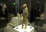 A mammoth ivory sculpture depicts a man with a lion's head, discovered at Stadel Cave, Baden-Wurttemberg, Germany, dates to around 40,000 years ago is seen on display in an exhibition 'Ice Age Art : arrival of the modern mind' at the British Museum in London, Tuesday, Feb. 5, 2013. The exhibition presents masterpieces created from the last Ice Age between 40,000 and 10,000 years ago, drawn from across Europe, by artists with modern minds and presented alongside modern works to illustrate the fundamental human desire to communicate and make art as a way of understanding ourselves and our place in the world. (AP Photo/Sang Tan)