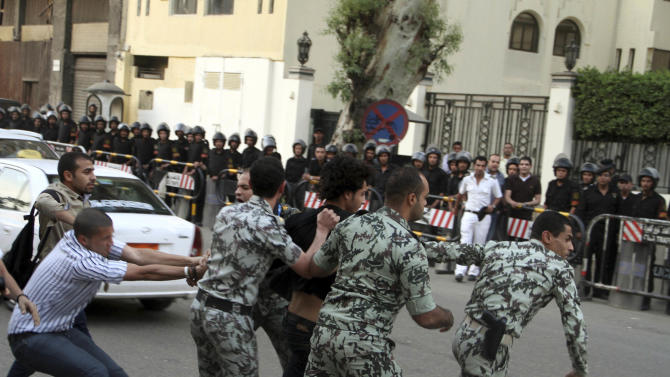 A protester is detained by security forces in front of the Saudi Embassy in Cairo, Egypt during a demonstration to demand the release of an Egyptian human rights lawyer detained in Saudi Arabia for allegedly insulting the kingdom's monarch, Saturday, April 28, 2012. Saudi Arabia said Saturday that it has closed embassy in Cairo because of protests over a detained Egyptian. (AP Photo/Ahmed Gomaa)