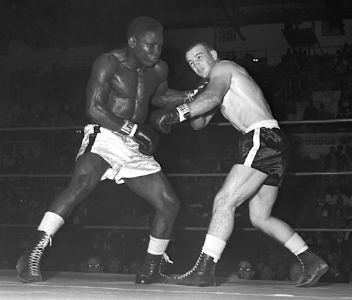 FILE - In this Sept. 12, 1964, file photo, former middleweight champion Dick Tiger, left, shakes up Don Fullmer with a hard left to the chin in a boxing bout in Cleveland. Fullmer, a former middleweight boxer who fought nine world champions and came within a fight of a world title himself, has died in Utah at the age of 72. His sons told the Deseret News that he died Saturday, Jan. 28, 2012, in West Jordan, Utah, after suffering from lymphocytic leukemia for 15 years. (AP Photo/Paul Shane, File)