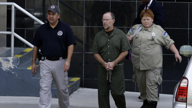 Former Enron CEO Jeffrey Skilling is escorted from the federal courthouse Friday, June 21, 2013, in Houston after being re-sentenced for his role in the energy giants' collapse. Skilling was resentenced to 14 years as part of a court-ordered reduction and a separate agreement with prosecutors. The decision brought a protracted legal conclusion to one of the most notorious U.S. financial scandals. Skilling has been in prison since 2006, when he was sentenced to more than 24 years by U.S. District Judge Sim Lake. But an appeals court vacated his prison term in 2009, ruling that a sentencing guideline was improperly applied. That meant a reduction of as much as nine years. (AP Photo/Pat Sullivan)