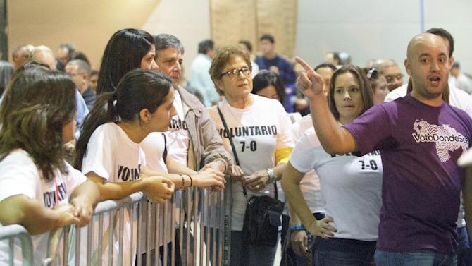 Carlos Herrera of Miami, right,  talks to election volunteers at the New Orleans Ernest Morial Convention Center, in New Orleans, Sunday, Oct. 7, 2012. Hundreds of Venezuelans living in the U.S. streamed into New Orleans on Sunday to cast ballots in the presidential election in their homeland, many of them determined to end the 13-year reign of Hugo Chavez. With the country's consulate in Miami closed, thousands of Venezuelans traveled by bus, car and plane to cast their votes at the consulate in New Orleans.  (AP Photo/Matthew Hinton)
