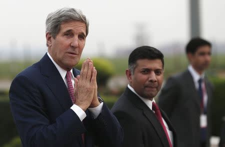 U.S. Secretary of State Kerry greets the media upon his arrival at the airport in New Delhi