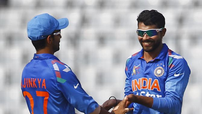 Indian cricketer Ravindra Jadeja, right, celebrates with his teammate Ajinkya Rahane after the dismissal of Afghan cricket player Asghar Stanikzai during the Asia Cup one-day international cricket tournament against India in Dhaka, Bangladesh, Wednesday, March 5, 2014. (AP Photo/A.M. Ahad)