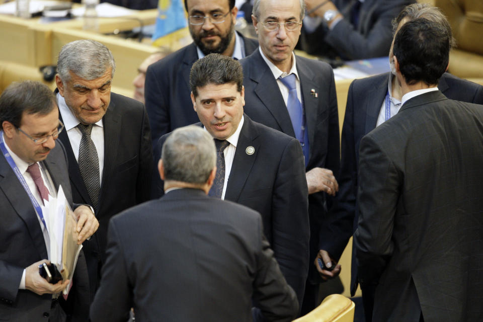Syria's prime minister, Wael Nader al-Halqi, center, arrives at conference hall of Nonaligned Movement summit in Tehran, Iran, Friday, Aug. 31, 2012. (AP Photo/Vahid Salemi)