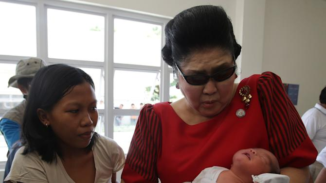 "In this May 5, 2013 photo, former Philippine First Lady Imelda Marcos, right, reacts as she carries a baby at a ""Mothering Center"" in Ilocos Norte province, northern Philippines. Twenty-seven years after her dictator husband was ousted by a public revolt, Imelda Marcos has emerged as the Philippines' ultimate political survivor: She was back on the campaign trail this week, dazzling voters with her bouffant hairstyle, oversized jewelry and big talk in a bid to keep her seat in Congress. (AP Photo/Aaron Favila)"