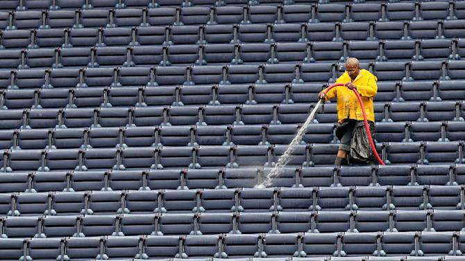 An Atlanta Braves stadium worker washes down seats in the upper deck Sunday, March 31, 2013, in preparation for opening day at Turner Field in Atlanta. The Braves play their season opener against the Phillies  on Monday. (AP Photo/Atlanta Journal-Constitution, Curtis Compton)