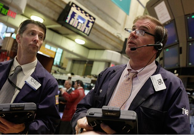 Traders Todd Ingrilli, left, and Jonathan Niles work on the floor of the New York Stock Exchange Monday, June 18, 2012. U.S. stocks are falling after the opening bell as Europe's debt crisis roils mar