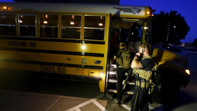 Police officers stand near a school bus used to evacuate attendees of the Muhammad Art Exhibit and Contest after a shooting in Garland, Texas