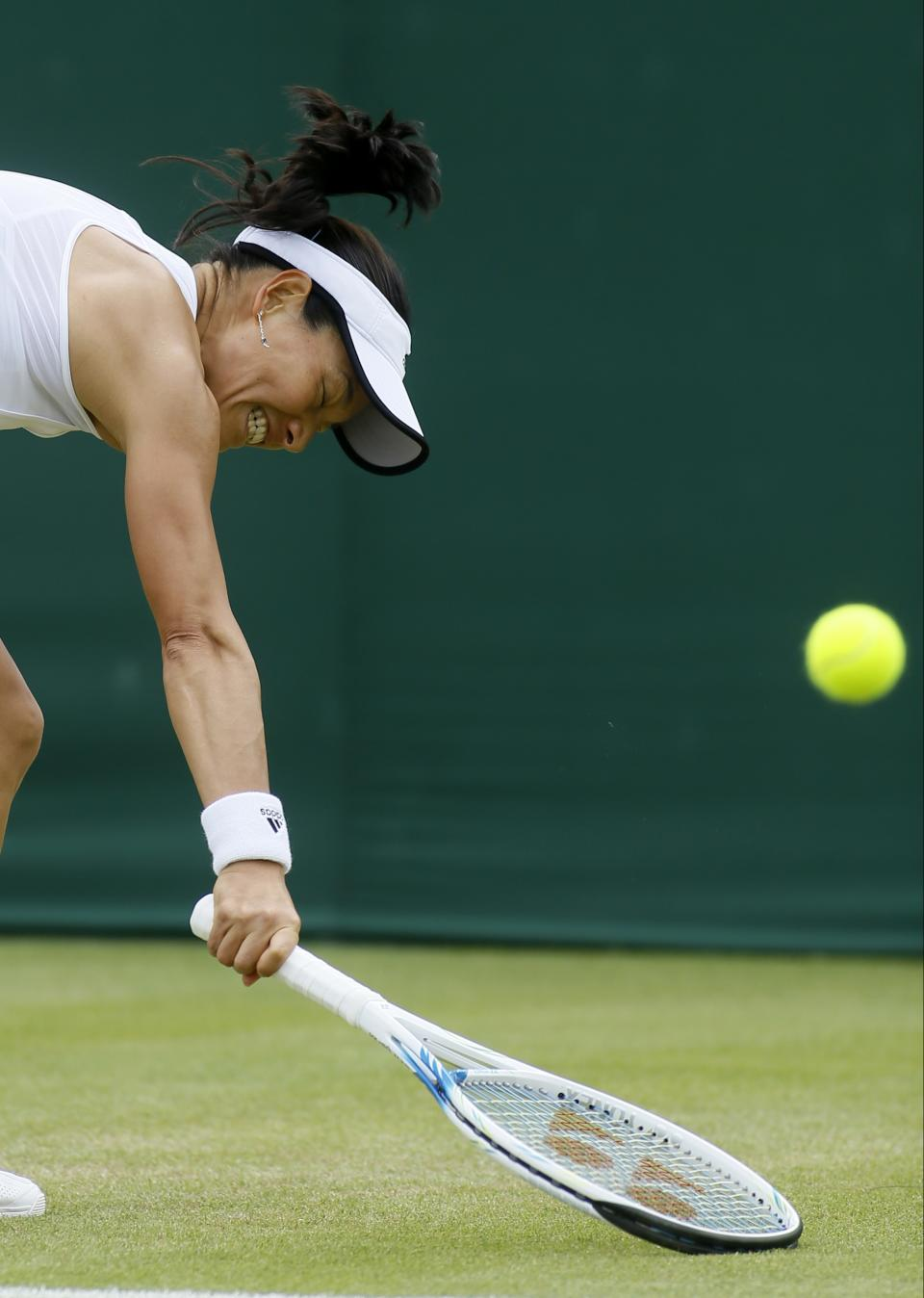 Kimiko Date-Krumm of Japan plays a return to Alexandra Cadantu of Romania in a Women's second round singles match at the All England Lawn Tennis Championships in Wimbledon, London, Thursday, June 27, 2013. (AP Photo/Kirsty Wigglesworth)