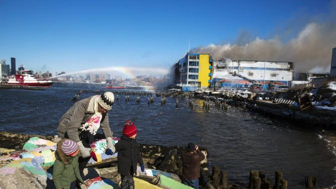 A father leads his two children away after watching members of the New York Fire Department battle a six alarm fire in a storage facility on the waterfront of the East River in New York