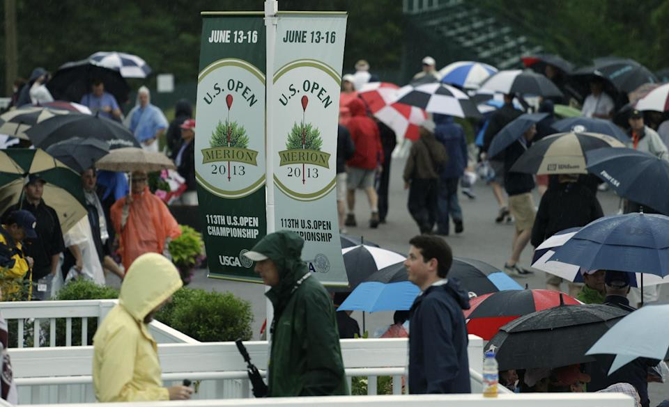 Spectators walk off the course as weather delays the first round of the U.S. Open golf tournament at Merion Golf Club, Thursday, June 13, 2013, in Ardmore, Pa. (AP Photo/Darron Cummings)