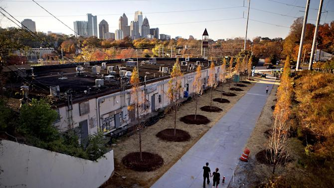 FILE- In this Nov. 20, 2012 file photo, a couple walks along the Atlanta BeltLine as the midtown skyline stands in the background in Atlanta. The Atlanta BeltLine is an urban redevelopment project that aims to turn an old 22-mile railroad corridor that rings the city's in-town neighborhoods into a network of trails, parks, affordable housing and, eventually, transit. So far, only the 2.2-mile Eastside Trail has opened, with skyline views and regularly changing public art installations providing added scenery for those who walk, bike and jog along the path. (AP Photo/David Goldman, File)