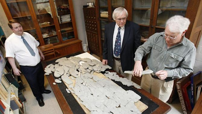 "In this April 20, 2012, photo, amateur paleontologist Ron Fine, of Dayton, Ohio, discusses the fossil he discovered with Carl Brett, center, and David Meyer, professors of Geology at the University of Cincinnati, at Caster Library on the campus in Cincinnati. Experts in the U.S. are trying to figure out what the 450 million-year-old fossil dubbed ""Godzillus"" used to be. The 150-pound fossil recovered last year in Kentucky is more than 6 feet long. (AP Photo/The Cincinnati Enquirer, Gary Landers)  MANDATORY CREDIT;  NO SALES"