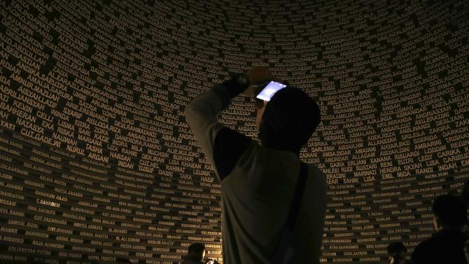 Visitors take pictures of the glowing names of tsunami victims at Aceh Tsunami Museum in Banda Aceh