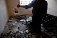 A man holds up a picture of President Bashar al-Assad at a former police station in Atareb after clashes between Syrian soldiers and Free Syrain Army near Aleppo. Rebels seized control of all of Syria&#39;s border crossings with Iraq, dealing a new blow to President Bashar al-Assad, as China and Russia dismayed the West by blocking UN action against his regime