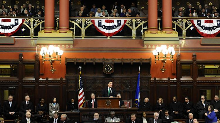"Connecticut Gov. Dannel P. Malloy, center, at podium, speaks to members of the House and the Senate in his State of the State address at the Capitol in Hartford, Conn., Wednesday, Jan. 9, 2013. Malloy urged state lawmakers Wednesday to work with him to prevent future tragedies like the Sandy Hook Elementary School shooting, but stressed that ""more guns are not the answer.""  Legislators also must grapple with a projected deficit of about $1.2 billion. (AP Photo/Jessica Hill)"