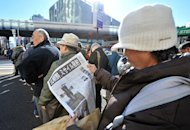 A woman is seen reading a special edition of a newspaper reporting on the rocket launch by North Korea, in Tokyo, on December 12, 2012. N.Korea successfully launched a long-range rocket in defiance of UN sanctions threats over what Pyongyang's critics have condemned as a disguised ballistic missile test