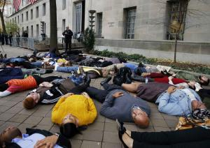 "Protestors stage a ""die-in"" as they rally …"