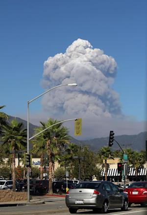 A plume of smoke rises from the San Gabriel Canyon area of the Angeles National Forest in the San Gabriel Mountains northeast of Los Angeles on Sunday, Sept, 2, 2012. A wildfire that broke out in the Angeles National Forest on Sunday forced the evacuation of thousands of visitors and sent a huge cloud of smoke that could be seen from throughout the Los Angeles basin. (AP Photo/John Antczak)