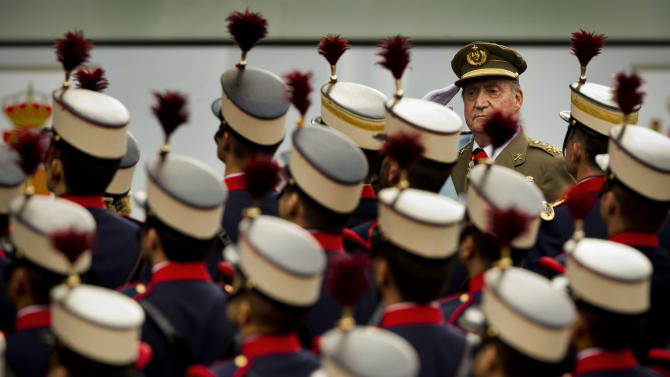 Spain's King Juan Carlos review troops before a military parade, during the holiday known as Dia de la Hispanidad, Spain's National Day, in Madrid, Friday, Oct. 12, 2012. King Juan Carlos presided over a much reduced parade that featured none of the usual fighter jets or tanks as they celebrate the day Christopher Columbus discovered America in the name of the Spanish Crown. (AP Photo/Daniel Ochoa de Olza)