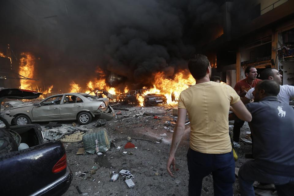 Lebanese citizens gather at the site of a car bomb explosion in southern Beirut, Lebanon, Thursday, Aug. 15, 2013. The powerful car bomb ripped through a southern Beirut neighborhood that is a stronghold of the militant group Hezbollah on Thursday, killing people and trapping others in burning buildings, the media said. (AP Photo/Hussein Malla)
