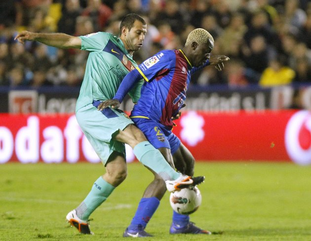 Levante's Kone and Barcelona's Mascherano fight for the ball during their Spanish first division soccer match in Valencia