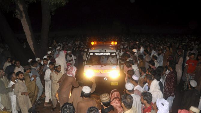 Supporters of Malik Ishaq wait for the arrival of his body for burial before his funeral in Rahimyarkhan
