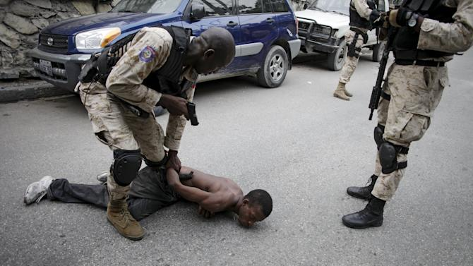 A National Police officer immobilizes a protestor carrying a machete during a demonstration against the results of the presidential elections in Port-au-Prince, Haiti